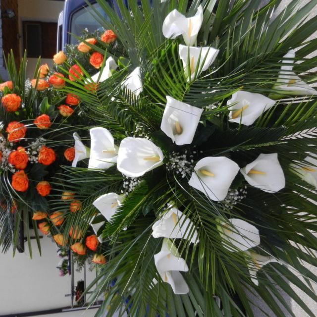 Wiązanka pogrzebowa z pomarańczowymi różami oraz białymi kaliami